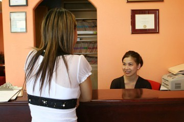 receptionist smiling behind her desk at a client
