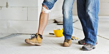 injured construction worker being supported by a coworker