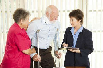 female attorney taking notes about a clients personal injury as he stands using crutches while wearing a neck brace and being supported by his wife