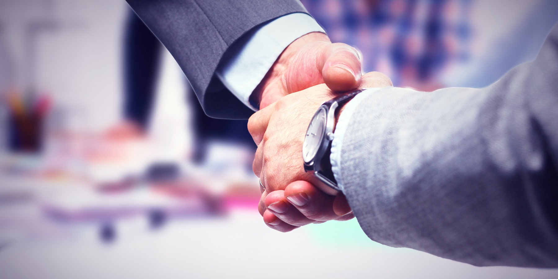 close up image of two business men shaking hands after forming a partnership