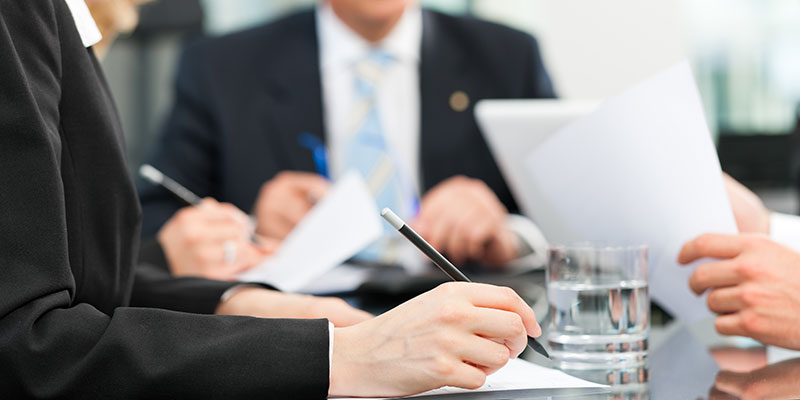 group of people dressed in business attire around a table having a discussion and taking notes and passing around paper