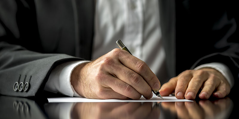 close up of a business man signing a document