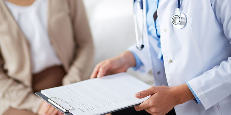 doctor holding a clipboard with a blank form on it while a patient sits nearby